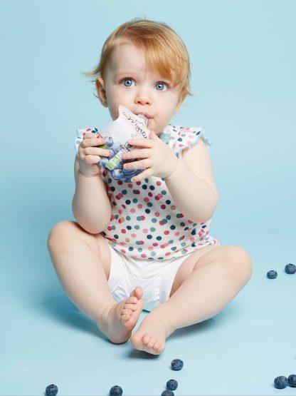 Bébé en habits d'été mettant dans sa bouche une gourde Popote à la myrtille, petits myrtilles éparpillées autour de lui, fond de l'image bleu