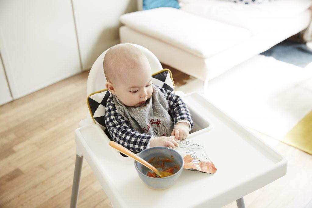 Bébé assis mangeant une popote dans un bol
