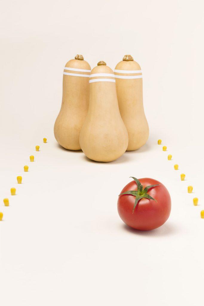 Photo de courges qui ressemblent à des quilles et d'une belle tomate rouge