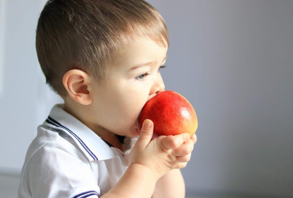 enfant mange qui mange pomme