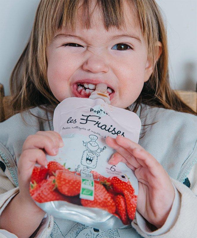 Un bébé mange sa compote à la fraise Popote